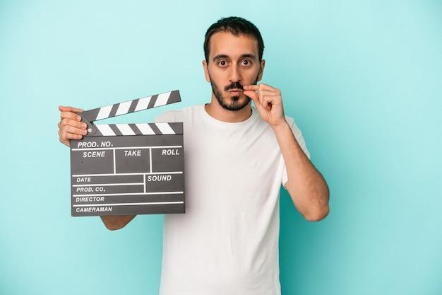Junger kaukasischer schauspielermann, der clapperboard lokalisiert auf blauem hintergrund mit fingern auf lippen hält, die ein geheimnis halten.