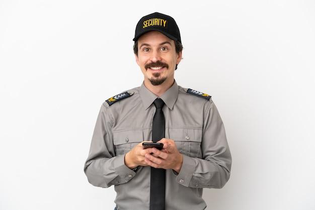 Junger kaukasischer sicherheitsmann isoliert auf weißem hintergrund, der eine nachricht mit dem handy sendet