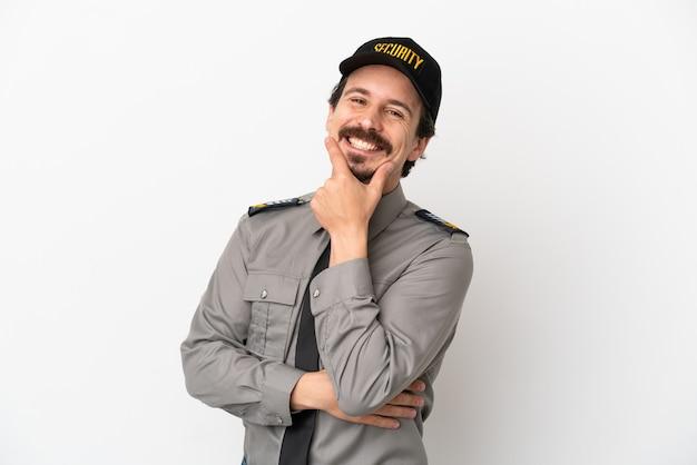 Junger kaukasischer sicherheitsmann isoliert auf weißem hintergrund lächelnd
