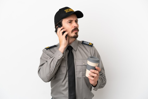 Junger kaukasischer sicherheitsmann isoliert auf weißem hintergrund mit kaffee zum mitnehmen und einem handy