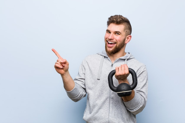 Junger kaukasischer sportler, der einen dummkopf lächelt hält, freundlich zeigend mit dem zeigefinger weg.