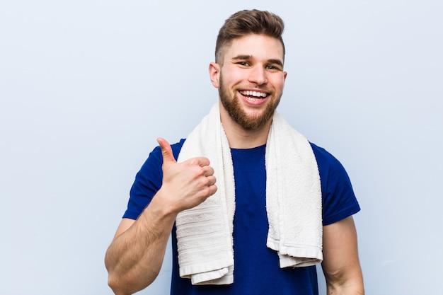 Junger kaukasischer sportler mit einem tuch oben lächelnd und daumen anhebend