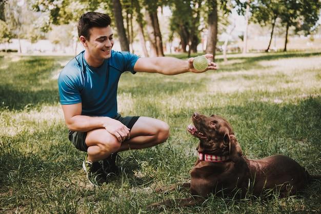 Junger kaukasischer sportler mit seinem hund im grünen park.
