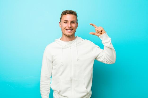 Junger kaukasischer sportmann, der etwas wenig mit zeigefingern hält, lächelnd und zuversichtlich.
