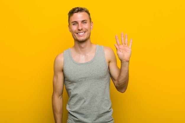 Junger kaukasischer sportmann, der fröhlich lächelt und nummer fünf mit den fingern zeigt.