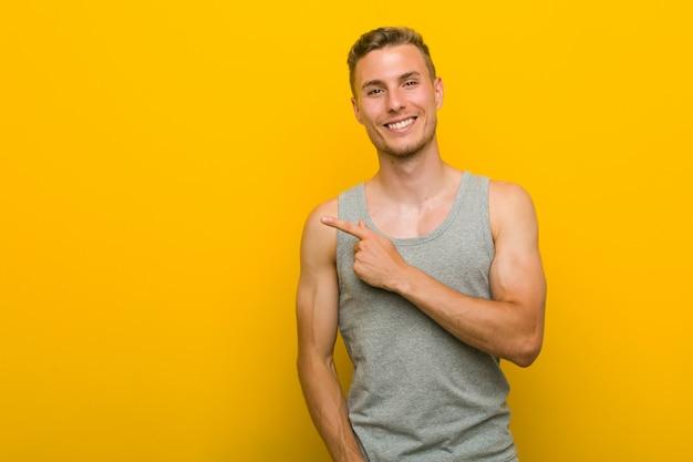 Junger kaukasischer sportmann, der lächelt und beiseite zeigt und etwas an der leeren stelle zeigt.