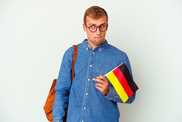 Junger kaukasischer student, der deutsch auf weißem hintergrund studiert, verwirrt, fühlt sich zweifelhaft und unsicher.