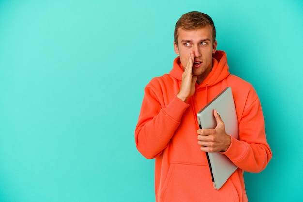 Junger kaukasischer student, der einen laptop isoliert auf blau hält, sagt eine geheime heiße bremsnachricht und schaut beiseite