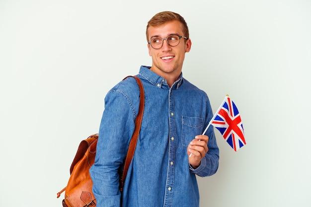 Junger kaukasischer student, der englisch isoliert auf weißem hintergrund studiert, sieht beiseite lächelnd, fröhlich und angenehm aus.