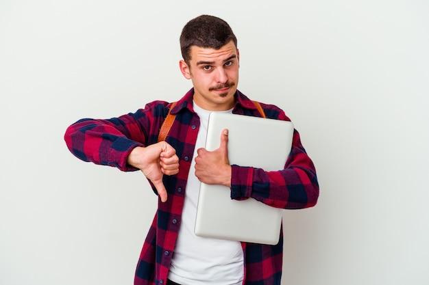 Junger kaukasischer studentenmann, der einen laptop auf weiß hält, der daumen hoch und daumen unten zeigt, schwieriges auswahlkonzept