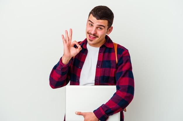 Junger kaukasischer studentenmann, der einen laptop lokalisiert auf weiß hält, zwinkert ein auge und hält eine okaygeste mit der hand.