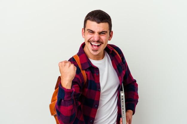 Junger kaukasischer studentenmann, der einen laptop lokalisiert auf weißem hintergrund hält, der sorglos und aufgeregt jubelt. siegeskonzept.