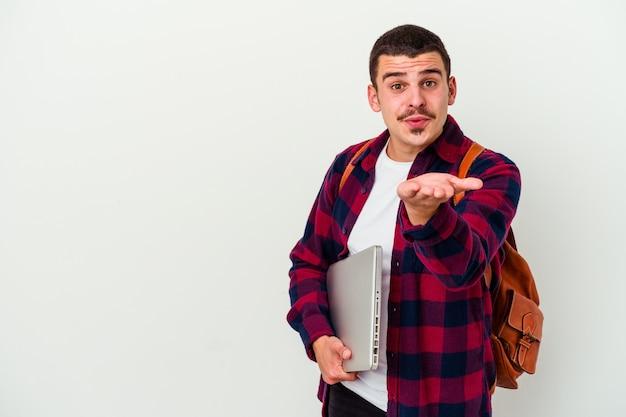 Junger kaukasischer studentenmann, der einen laptop lokalisiert auf weißen wandfaltenlippen hält und palmen hält, um luftkuss zu senden.