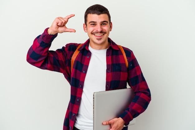 Junger kaukasischer studentenmann, der einen laptop lokalisiert auf weißer wand hält, die etwas wenig mit zeigefingern hält, lächelnd und zuversichtlich.