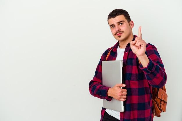 Junger kaukasischer studentenmann, der einen laptop lokalisiert auf weißer wand zeigt, die nummer eins mit finger zeigt.