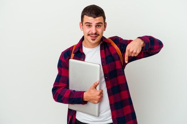 Junger kaukasischer studentenmann, der einen laptop lokalisiert auf weißer wand zeigt, zeigt mit den fingern nach unten, positives gefühl.