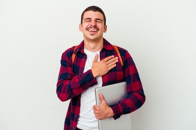 Junger kaukasischer studentenmann, der einen laptop lokalisiert hält, der auf weißem hintergrund lacht und hände auf herz hält, konzept des glücks.