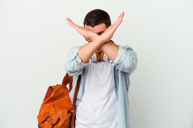 Junger kaukasischer studentenmann, der musik auf weiß hört, der zwei arme verschränkt hält, verweigerungskonzept.