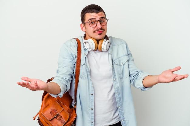 Junger kaukasischer studentenmann, der musik einzeln auf weiß hört und zweifelt und die schultern in fragender geste zuckt.