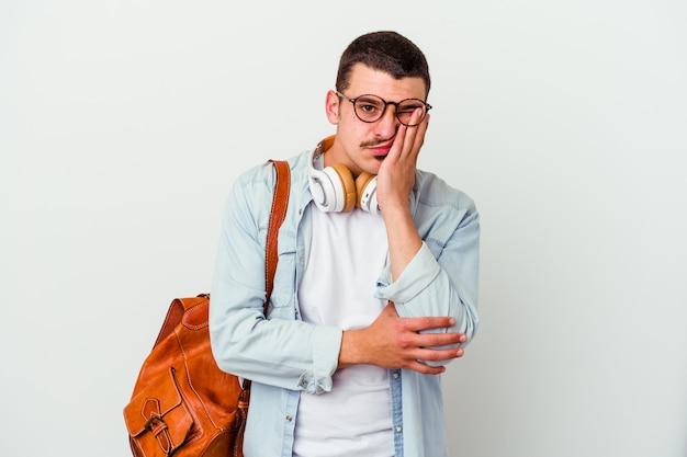 Junger kaukasischer studentenmann, der musik einzeln auf weißem hintergrund hört, der gelangweilt ist, müde ist und einen entspannungstag braucht.