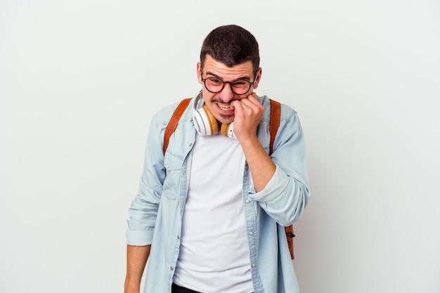 Junger kaukasischer studentenmann, der musik hört, die auf weiße wand isoliert fingernägel beißt, nervös und sehr besorgt