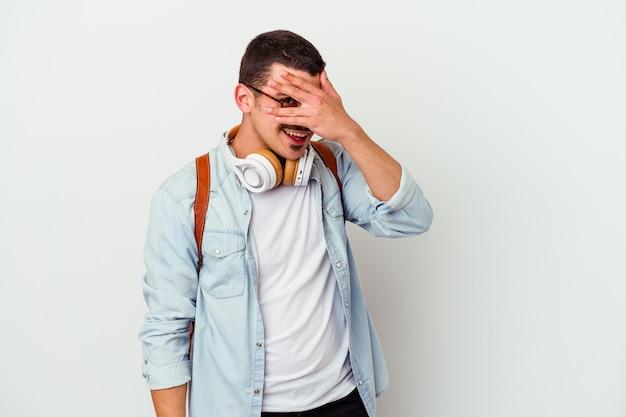 Junger kaukasischer studentenmann, der musik hört, die auf weißem hintergrund lokalisiert wird, blinkt an der kamera durch finger, verlegenes bedeckendes gesicht.