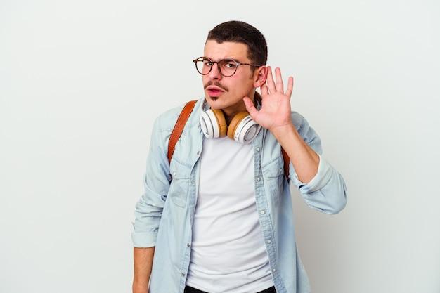 Junger kaukasischer studentenmann, der musik hört, die auf weißem hintergrund lokalisiert wird, der versucht, einen klatsch zu hören.