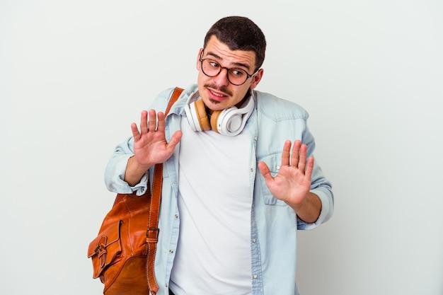 Junger kaukasischer studentenmann, der musik hört, die auf weißer wand isoliert ist, die jemanden ablehnt, der eine geste des ekels zeigt