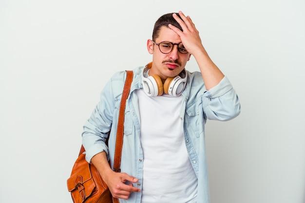 Junger kaukasischer studentenmann, der musik hört, die auf weißer wand isoliert müde und sehr schläfrig ist, die hand auf kopf hält.