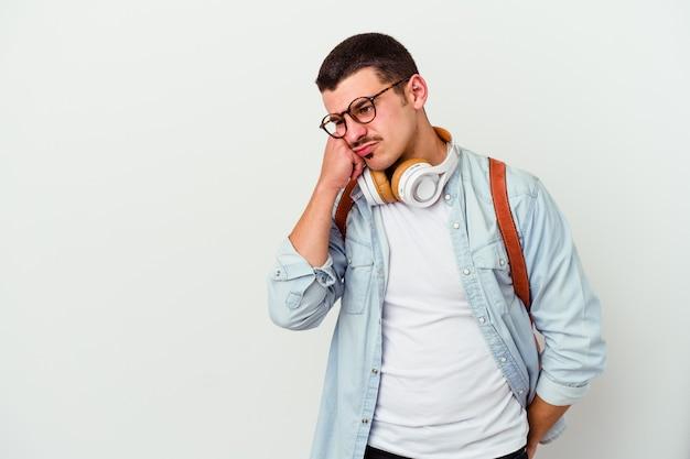 Junger kaukasischer studentenmann, der musik lokalisiert auf weißer wand hört, die traurig und nachdenklich fühlt und kopierraum betrachtet.