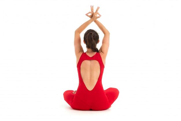 Junger kaukasischer turner mit athletischem körper sitzt auf einem boden, macht yoga und meditiert
