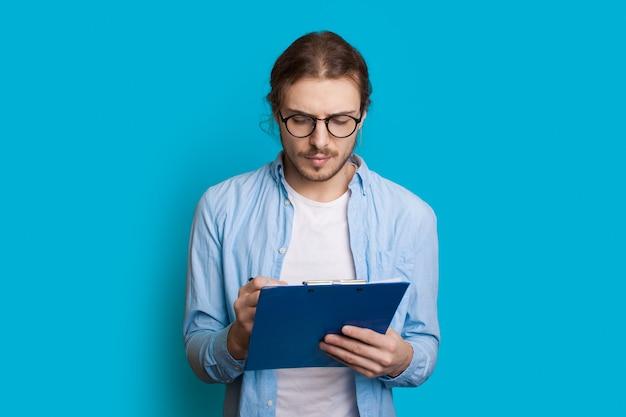 Junger kaukasischer unternehmer mit langen haaren und bart, die etwas auf eine blaue wand schreiben