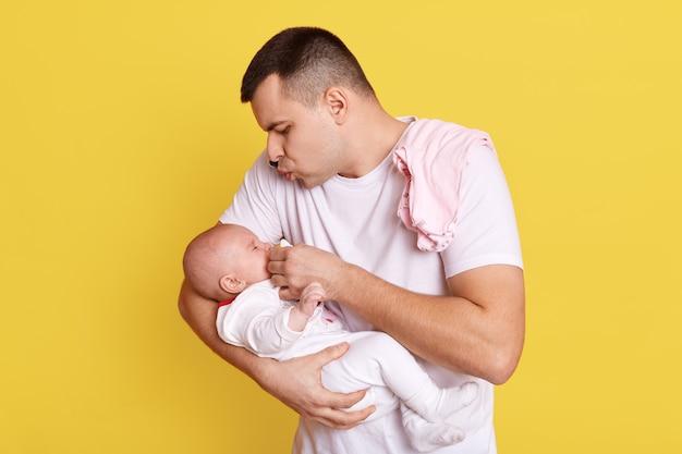 Junger kaukasischer vater gibt baby schnuller, blick auf ihre tochter oder sohn mit großer liebe, kerl trägt weißes t-shirt, posiert isoliert über gelber wand.
