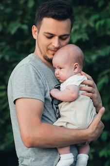 Junger kaukasischer vati mit bart umarmt neugeborenen babysohn