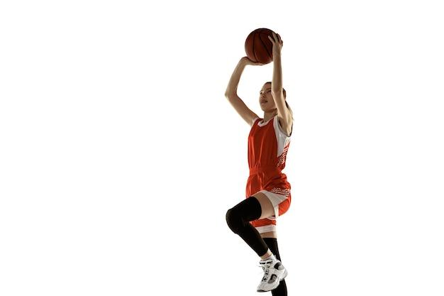 Junger kaukasischer weiblicher basketballspieler in aktion, bewegung im sprung lokalisiert auf weißem hintergrund. redhair sportliches mädchen. konzept von sport, bewegung, energie und dynamischem, gesundem lebensstil. ausbildung.