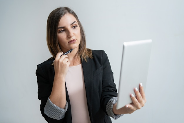 Junger kaukasischer weiblicher manager, der tablette hält und kinn berührt