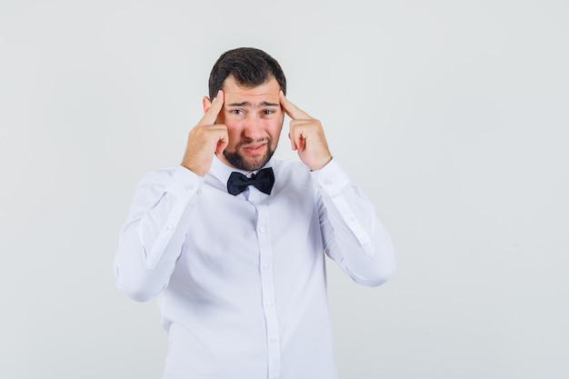 Junger kellner, der finger auf schläfen hält und kopfschmerzen in der vorderansicht des weißen hemdes hat.