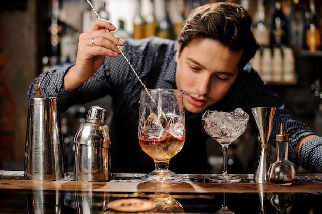 Junger kellner, der frisches alkoholisches cocktail mit sirup rührt