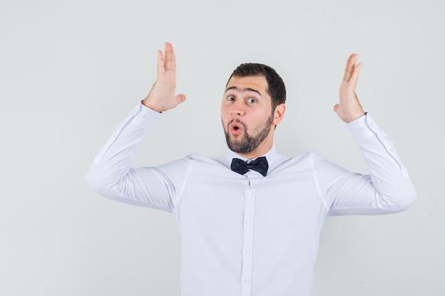 Junger kellner, der größenzeichen im weißen hemd zeigt und erstaunt, vorderansicht schaut.