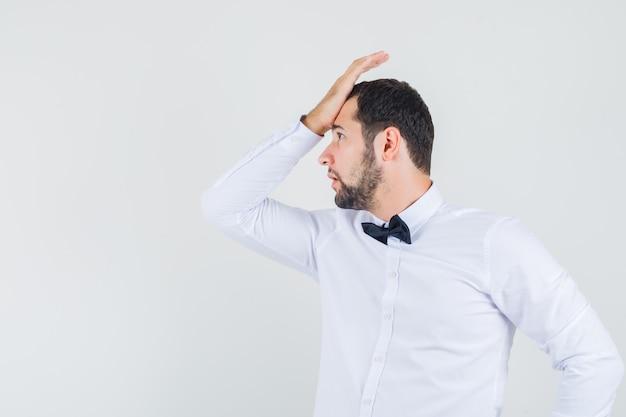 Junger kellner, der handfläche auf stirn im weißen hemd hält und vergesslich schaut. vorderansicht.