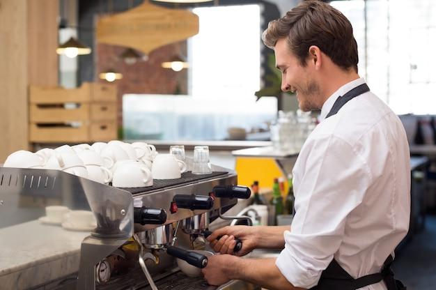 Junger kellner, der kaffee am kaffeehaus kocht