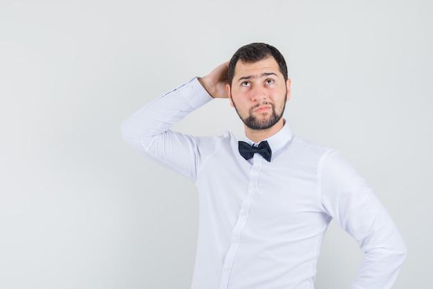 Junger kellner, der mit hand hinter kopf im weißen hemd aufschaut und nachdenklich schaut. vorderansicht.