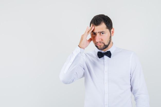 Junger kellner im weißen hemd, das kopfschmerzen hat und traurige vorderansicht schaut.