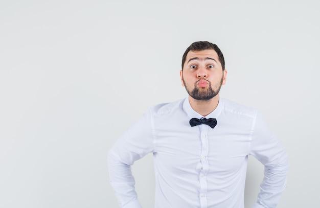Junger kellner im weißen hemd schmollt lippen und schaut geliebt, vorderansicht.