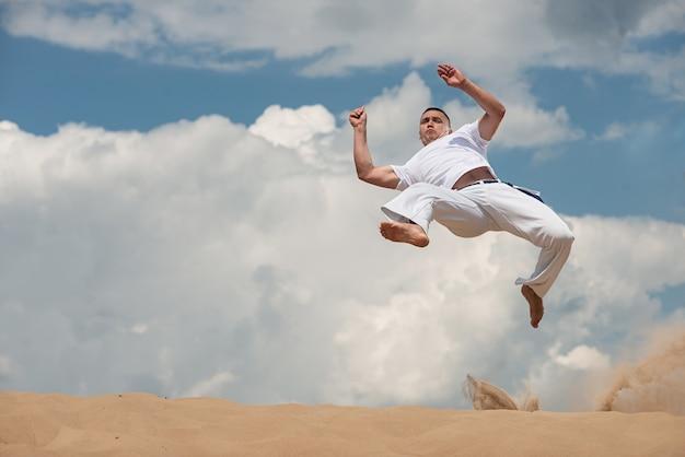 Junger kerl bildet capoeira auf himmel backround aus. ein mann führt den tritt im sprung martialisch aus