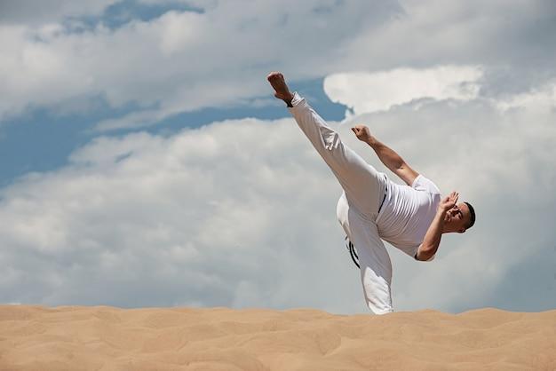 Junger kerl bildet capoeira auf himmel backround aus. ein mann führt den tritt martialisch aus
