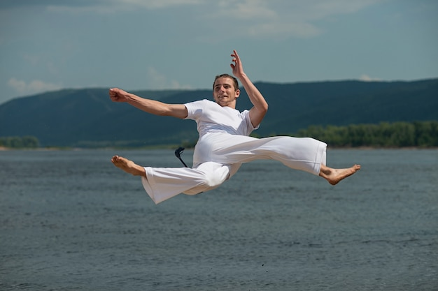 Junger kerl bildet capoeira im himmel aus