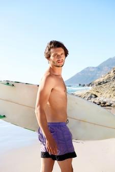 Junger kerl, der am strand mit surfbrett steht