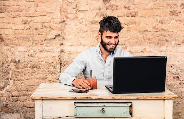 Junger kerl, der am weinleseschreibtisch mit laptop sitzt