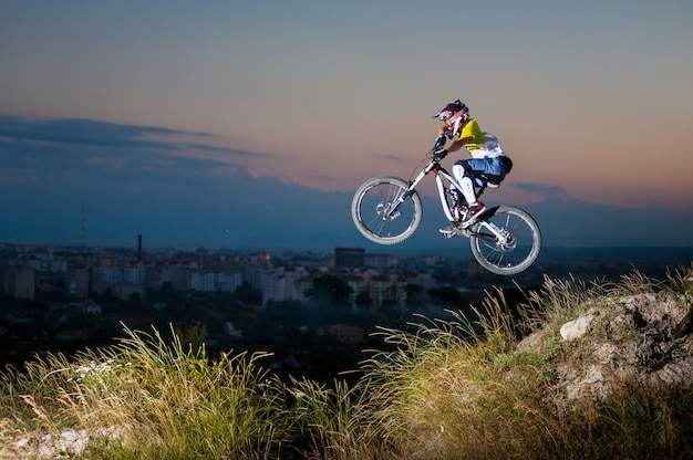 Junger kerl, der auf eine mountainbike auf der steigung hochspringt